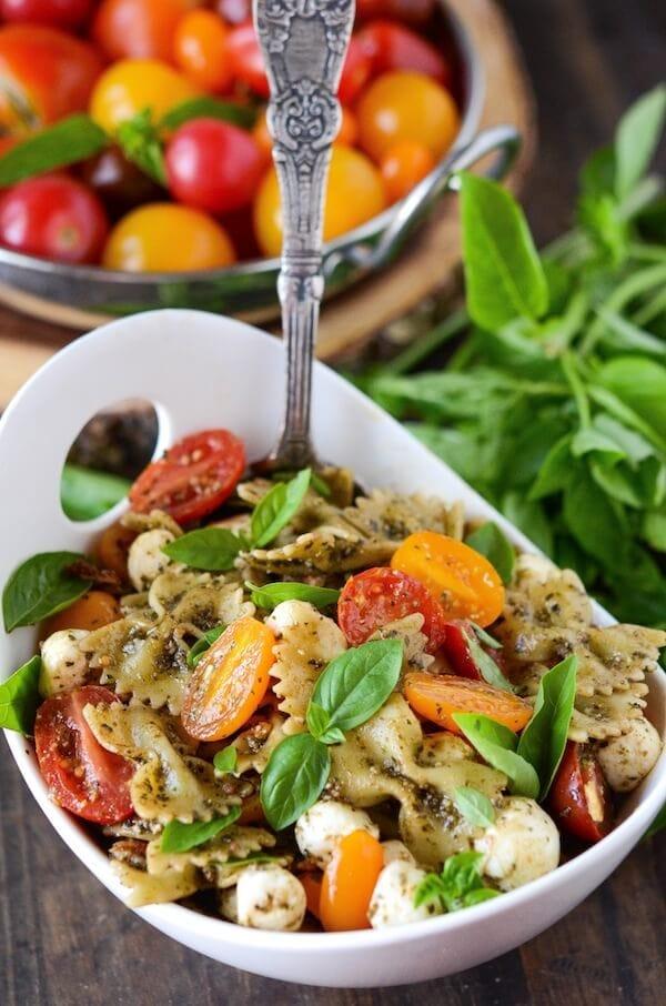 Pesto Bacon Pasta Salad! Bowtie pasta in a basil pesto sauce, tossed with bacon, fresh mozzarella and cherry tomatoes!