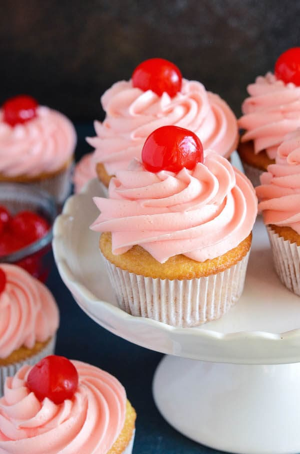 Maraschino Cherry Cupcakes: Sweet almond scented cupcakes are filled with bites of red maraschino cherries and topped with a gorgeous bright maraschino cherry buttercream!