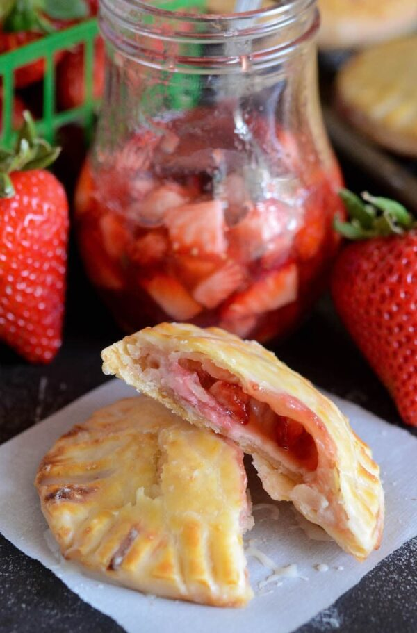 Strawberries & Cream Hand Pies are individually glazed small pies stuffed with strawberry preserves, fresh strawberries and sweetened vanilla cream cheese.