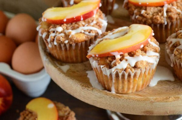Peaches & Cream Streusel Muffins: tender muffins loaded with fresh peaches and cinnamon are topped with a sweet streusel topping and creamy vanilla icing.